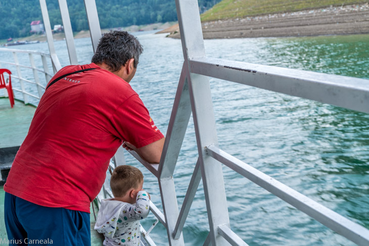 Father and son looking at the lake shore